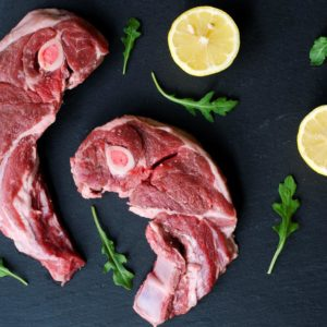 A lamb shoulder chops. Raw meat with lemon and asparagus on black stone.