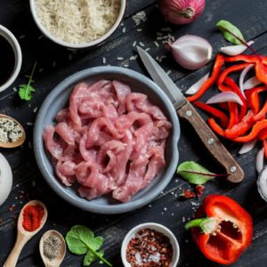 Ingredients for cooking meat stir fry with vegetables and rice - raw meat, sweet red pepper, red onion, rice, spices, on dark wooden background. Top view