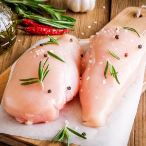 raw chicken fillet with garlic, pepper and rosemary on a wooden background