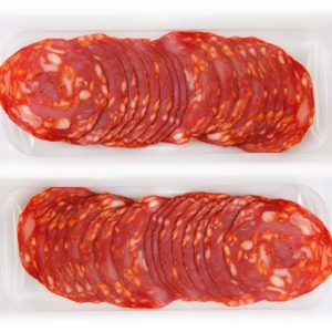 Some cut slices of red iberian chorizo on the package. Isolated over white background