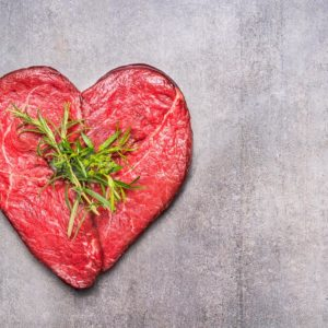 Heart shape raw meat with herbs and text on gray concrete background , top view, horizontal