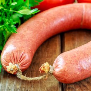 Beef sausage on wooden background with parsley and tomato